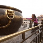 Girl Trying to Touch a Huge Bronze Cauldron in the Forbidden City, Beijing