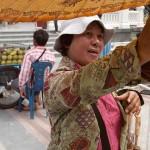 Woman Selling Sun Parasols at Wat Traimit, Bangkok, Thailand